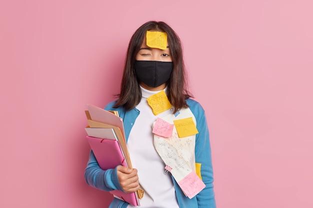 ウイルス拡散の防止。真面目なブルネットの女性は、仕事をするのに忙しい黒い使い捨てのフェイスマスクを身に着けています。