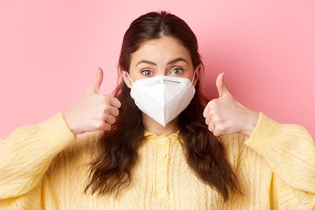 예방 조치, 건강 관리 개념. 젊은 여자의 얼굴 초상화를 닫습니다 엄지 손가락을 보여주고, covid-19에서 의료용 호흡기를 착용하고, 분홍색 벽에 서 있습니다.