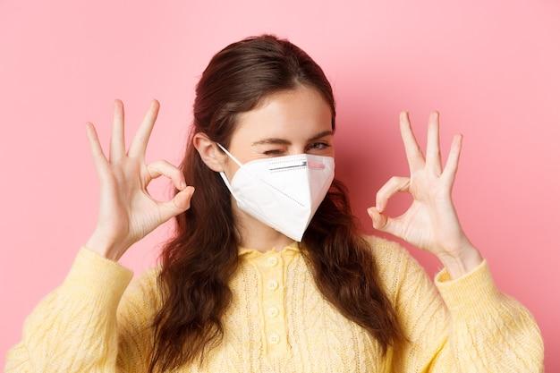予防策、ヘルスケアの概念。自信を持っている女の子のクローズアップは大丈夫だと言います、ウィンクとうなずき、すべてが大丈夫であることを保証し、物事は制御され、ピンクの壁に立ち向かいます。