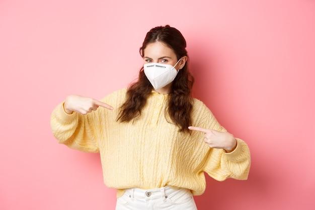 Профилактические меры концепция здравоохранения молодая счастливая женщина защищает себя от covid с помощью медицинских респираторов на груди, показывает ваш логотип или рекламный текст на розовой стене