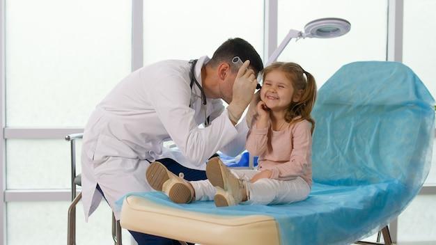 Профилактический медицинский осмотр ребенка в поликлинике. заботливый врач осматривает ухо маленькой девочки с помощью специального прибора. комфортное пребывание ребенка в клинике.