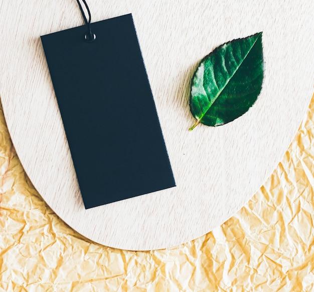 Ценник и зеленый лист на фоне природных материалов устойчивой моды и концепции бренда