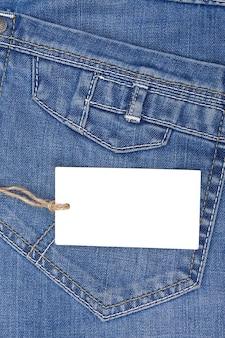 Ценник поверх синих джинсов с текстурированным карманом