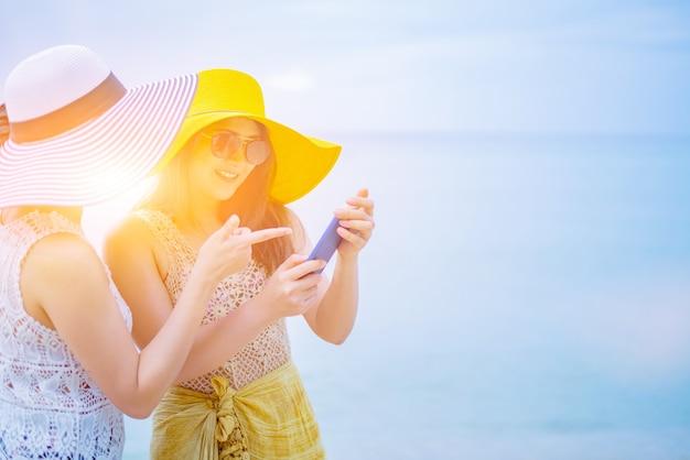 여름 해변의 프라이드와 lgbtq+. 양성애자와 동성애자 사랑의 커플. 작업 사진에 스마트 폰을 사용합니다.