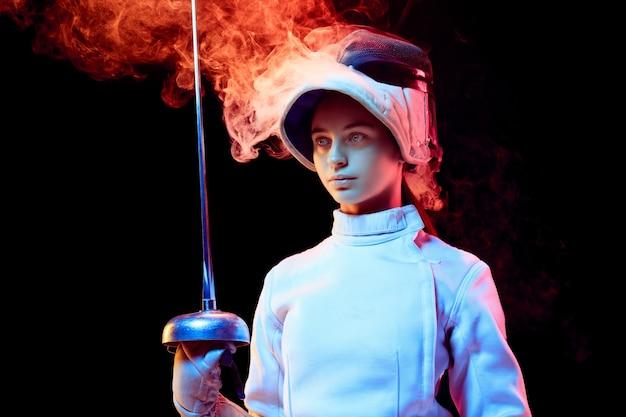 Orgoglio. teen ragazza in costume da scherma con la spada in mano isolato su sfondo nero, fumo illuminato al neon. pratica e allenamento in movimento, azione. copyspace. sport, gioventù, stile di vita sano.
