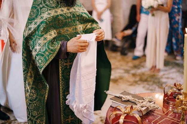 Священник на свадьбе держит белое полотенце