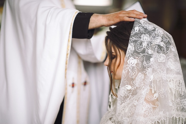 Priest blesses bride during the ceremony in church