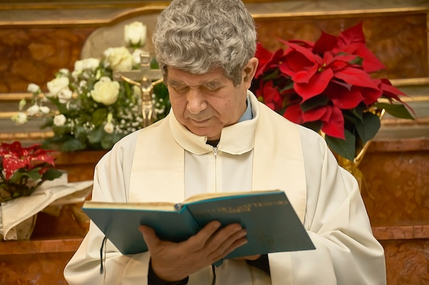 Priest celebrates the liturgy in a catholic church in italy