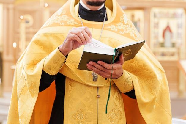 Священник руки, держа книгу библии на фоне традиционной православной церкви