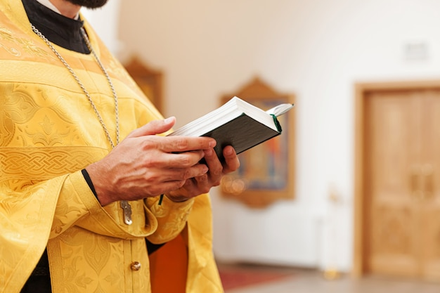 Priest hands holding holy bible book in traditional orthodox church
