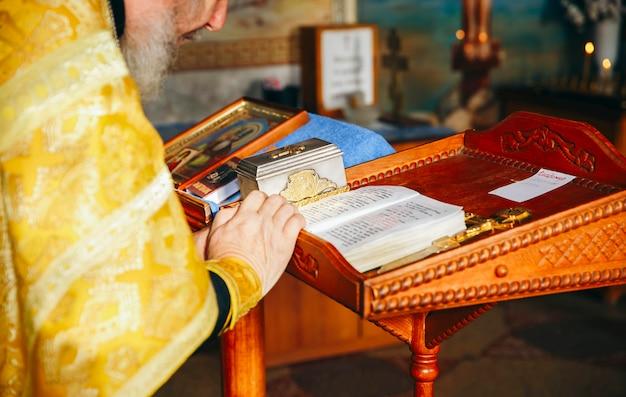 Священник держит крест в церемонии крещения в церкви