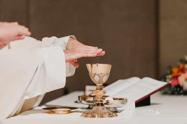 Priest holding the goblet during a wedding ceremony nuptial mass. religion concept