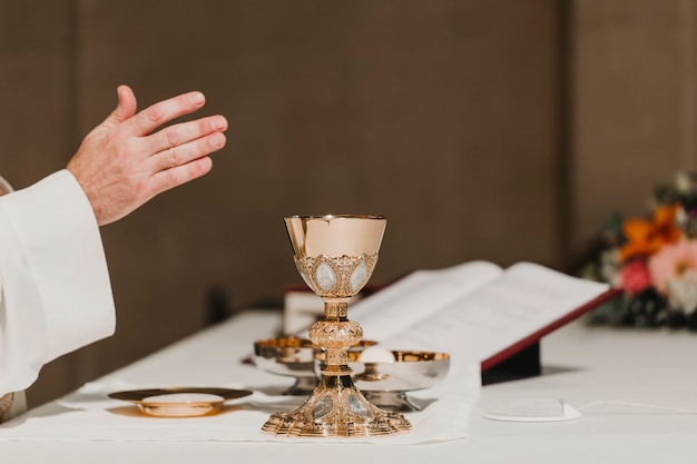 Священник держит кубок во время свадебной церемонии брачной мессы. концепция религии