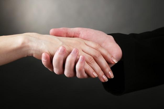 黒に、女性の手を握っている司祭
