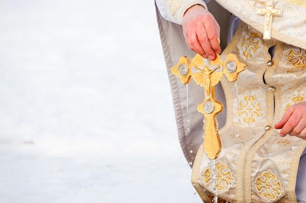 司祭は金色の十字架を手に持っています。スペースをコピーします。