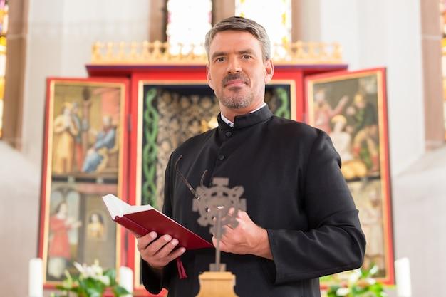 Священник в церкви с библией перед алтарем