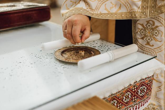 司祭は顔のないトレーから結婚指輪を取っています