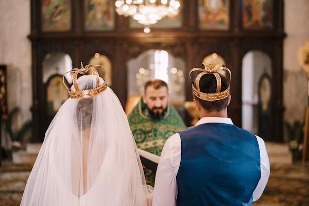 Священник женится на женихе и невесте в церкви, вид сзади