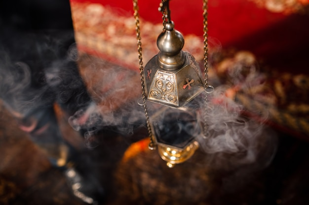 Priest's censer hangs on an old wall in the orthodox church. copper incense with burning coal inside. service in the concept of the orthodox church. adoration