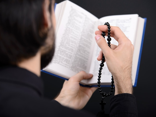 Priest with holy bible. portrait of priest reading bible