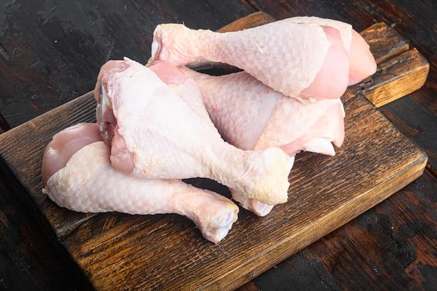 Первичный вырез из сырых куриных окорочков, с куриными бедрами и голеньями, на деревянной разделочной доске, на старом темном деревянном столе