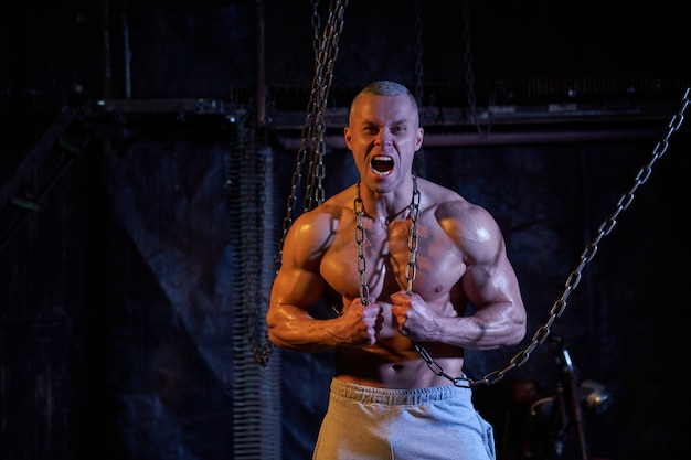 Primal instinct. angry muscular man screaming at camera and breaking chains on chest, dark background