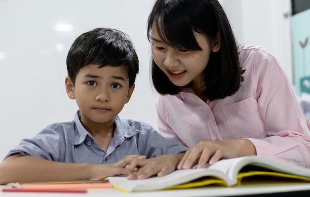Первичные азиатские студенты. азиатский мальчик в униформе читает книгу в школе во время урока