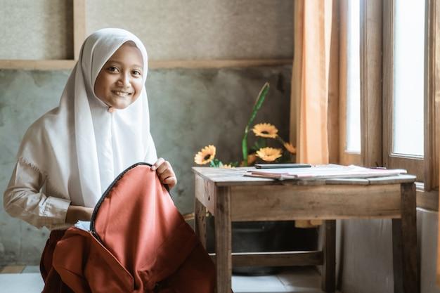 朝学校に行く前に自宅で本を準備しているインドネシアの小学生
