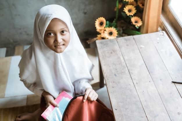 Ученица начальной школы из индонезии готовит книгу дома перед тем, как пойти в школу утром