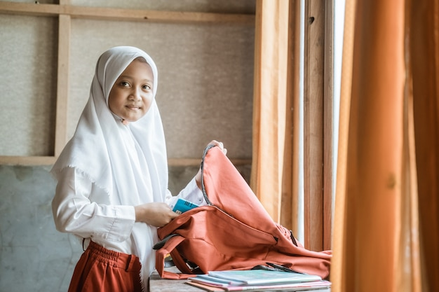 Primary indonesian school student preparing her book at home before going to school in the morning