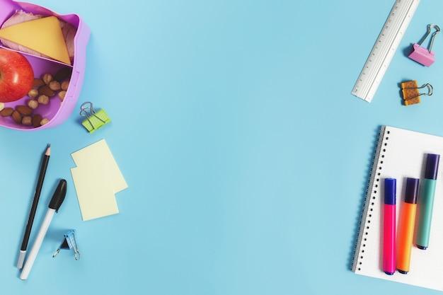 Концепция плоской планировки начальной школы с различными школьными принадлежностями, блокнотом, ручкой, карандашом, рынками, наклейками, скрепками и ланч-боксом с бутербродом, орехами и яблоком на синей поверхности