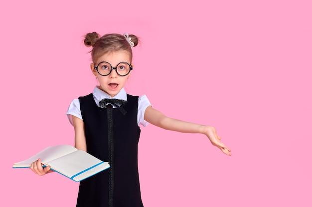 Ученица начальной школы в форме, круглых очках без линз держит в руках блокнот и поднимает руку в сторону с эмоцией вопроса на лице, позируя на розовом пространстве.