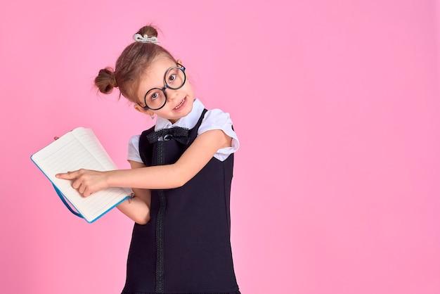 Ученица начальной школы в форме, круглых очках без линз держит в руках блокнот и указывает пальцем на пустую страницу на розовом пространстве в студии