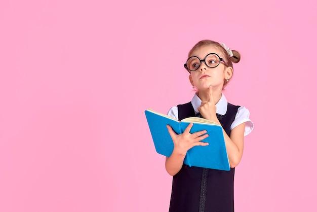Девочка начальной школы в форме, круглых очках без линз держит в руках тетрадь с задумчивым чувством на лице, позирует на розовом пространстве в студии