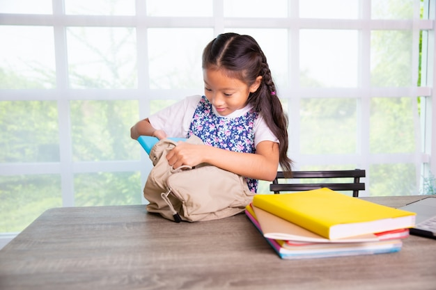Primary school girl packing books to the bags