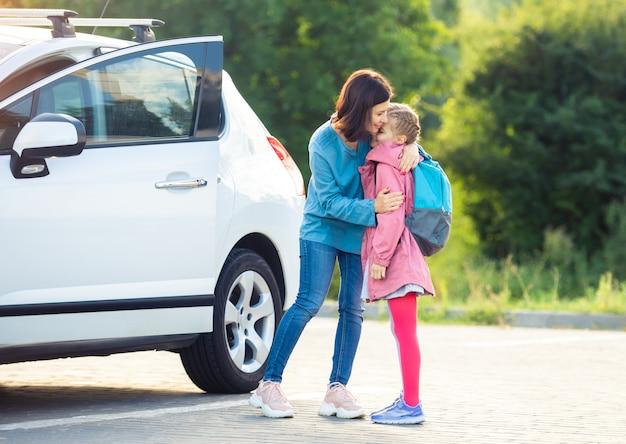 駐車場で母親に別れを告げる小学生の女の子