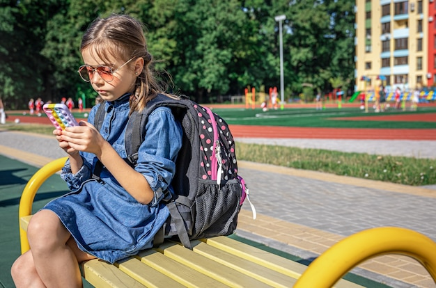 A primary school student with a backpack, uses a smartphone, sitting near the school.