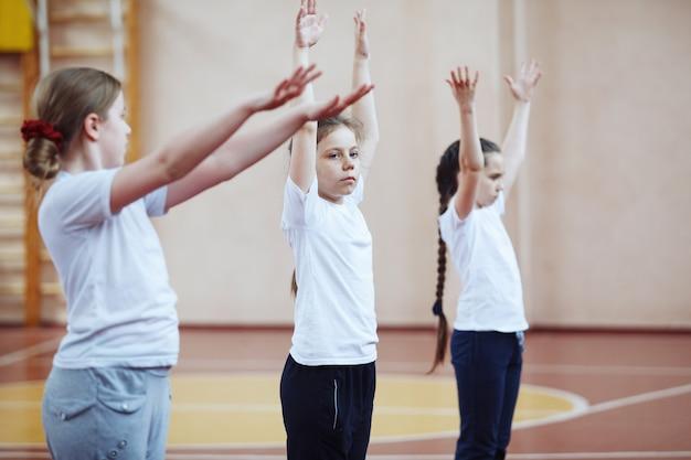 Ученики начальной школы на уроке спорта в помещении. дети выполняют гимнастические упражнения.