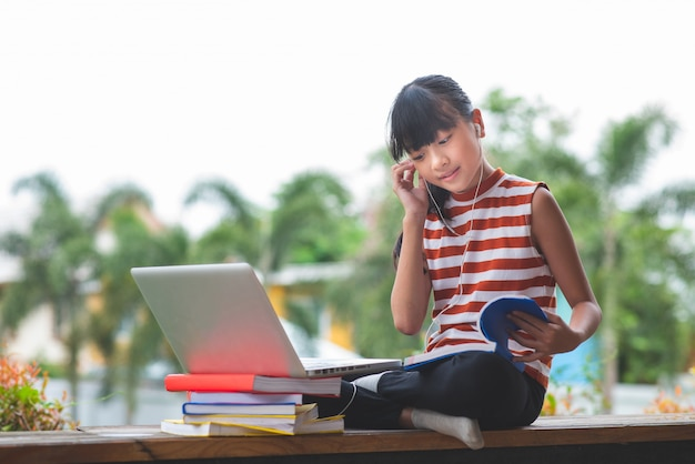Primary school students in asia sit and study at a distance from home.online education concept