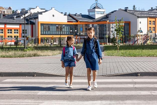 Учащиеся начальной школы возвращаются домой после школы, в первый день учебы, обратно в школу.