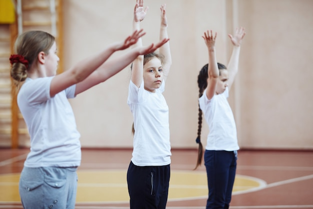 Primary school students a sport lesson indoors. children perform gymnastic exercises.