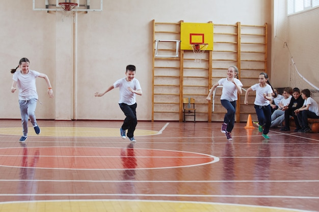 Primary school students a sport lesson indoors. children run and play mobile games.