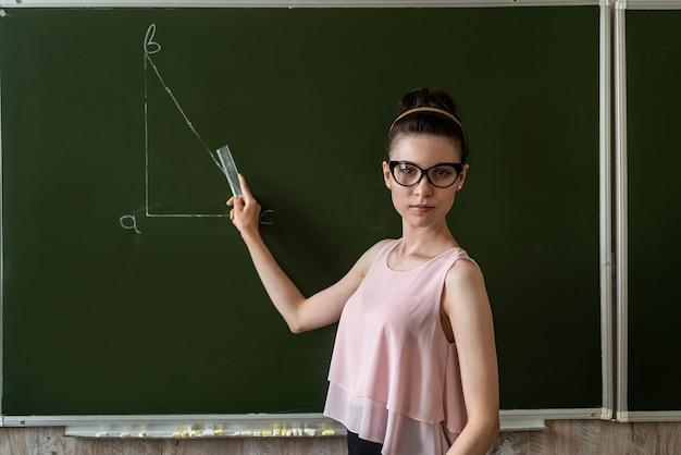 Учитель начальных классов возле доски и рисует треугольник