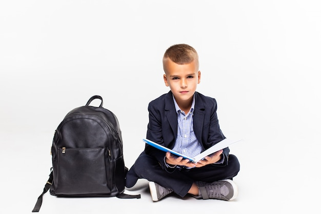Primary schoolboy sitting on floor and reading isolated on white wall