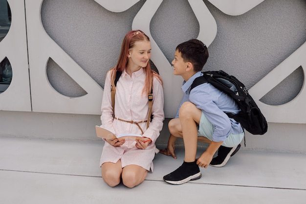Primary secondary education, school, the concept of friendship - two students boy and a teenage girl with backpacks are sitting, talking after school
