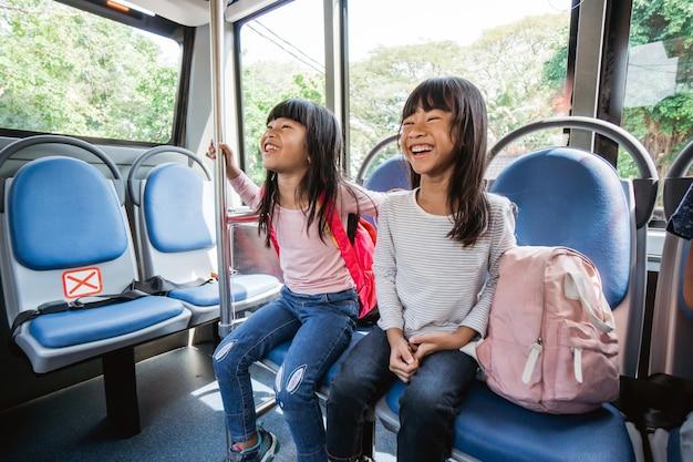 一緒にバスの公共交通機関で通学する小学生