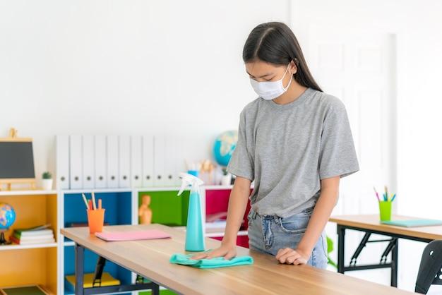 マスクとワイプでテーブルを掃除する小学生