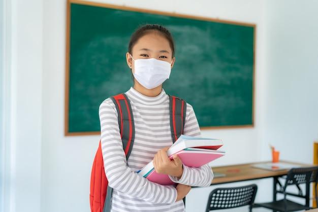 Ученик начальной школы с рюкзаком и книгами в маске