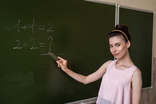 칠판에 쓰여진 초등 교사는 하나를 추가합니다. 초등학교