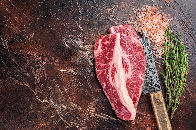 도살용 식칼에 블랙 앵거스 쇠고기 스테이크 생 스트립로인 또는 뉴욕을 얹습니다. 어두운 배경입니다. 평면도. 공간을 복사합니다.
